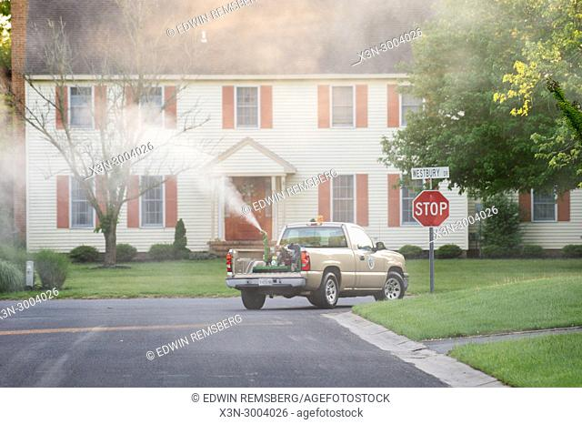 Salisbury Maryland USA - Mosquito Control Truck drives through suburban neighborhood spraying insecticide to control mosquito population