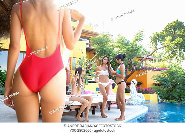 Pool Party with four young attractive hispanic women enjoying drinks and a conversation at upscale residential villa in Puerto Vallarta, Mexico