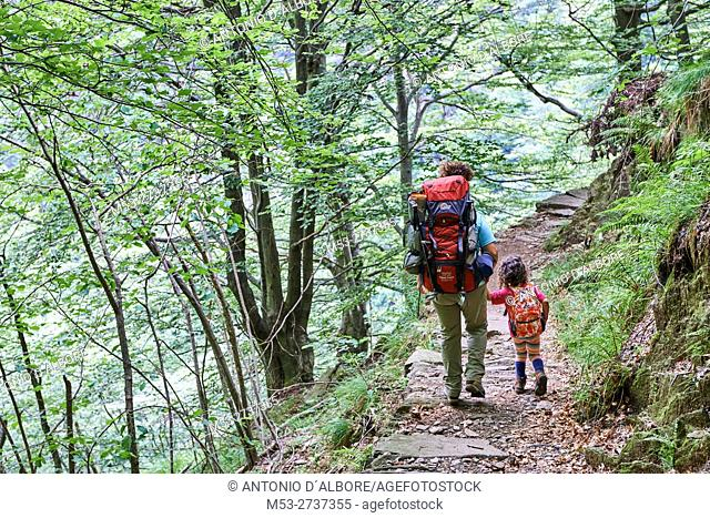 Mother and daughter hiking on a mountain trail in Val Grande National Park. Verbano-Cusio-Ossola Province. Piemonte. Italy