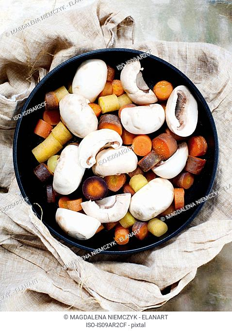 Steamed carrots and mushrooms in pan