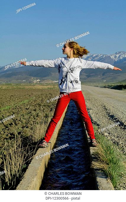 Teenage girl standing over a small canal of water with arms outstretched; Andalusia, Spain