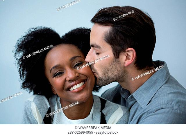 Man kissing on the cheek of woman