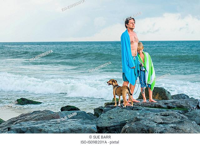 Father and son standing on rocks by sea, beach towels draped around them, pet dog beside them