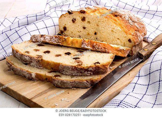 sliceed irish raisin soda bread with knife on a wooden board