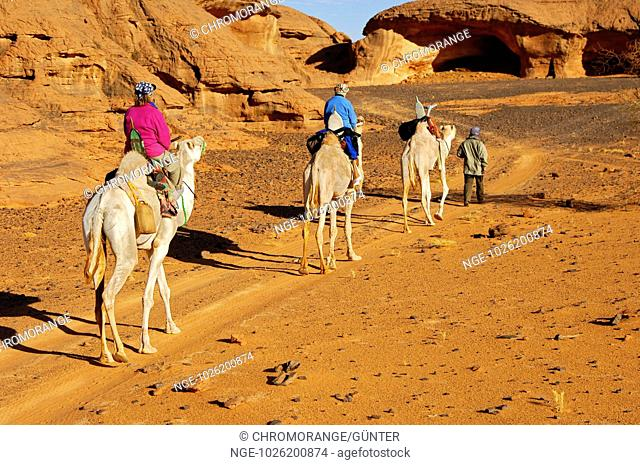 Tourists on a camel excursion in a wadi of the Acacus Mountains, Sahara desert, Libya