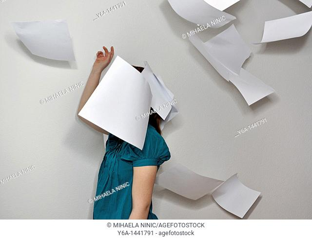 Young woman throwing paperwork in air