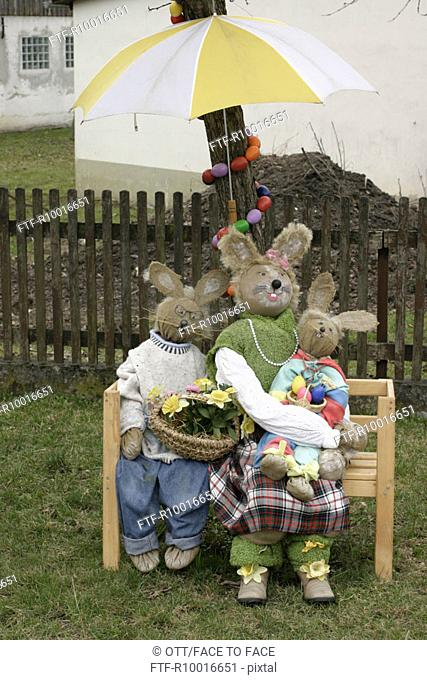 A family of dummy rabbits is decorated on the bench under the umbrella