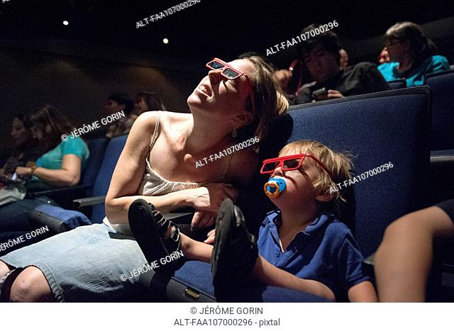 Mother and toddler son watching 3-D movie in theater