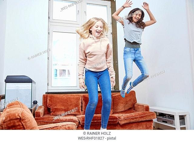 Two happy girls jumping and dancing at home