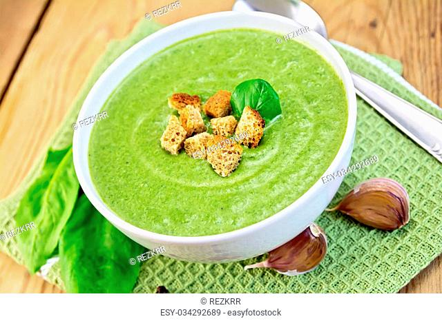 Green soup puree in a bowl with green spinach leaves, spoon, garlic on a napkin on a wooden boards background