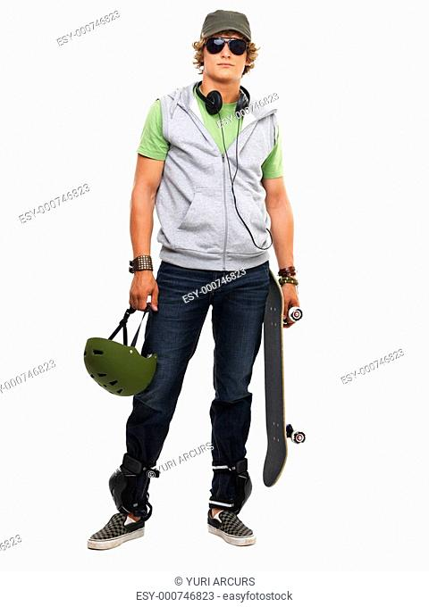 Portrait of a guy standing with skateboard and helmet in hand against white background