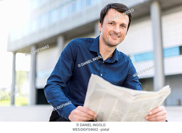 Portrait of smiling businessman with newspaper in the city