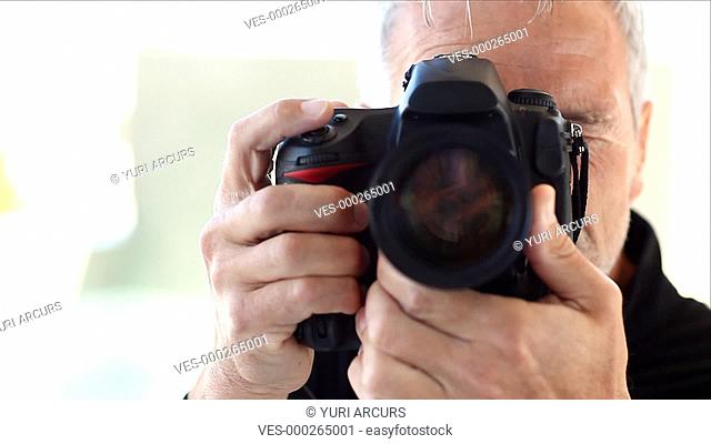 A mature man taking pictures of you with his DSLR camera