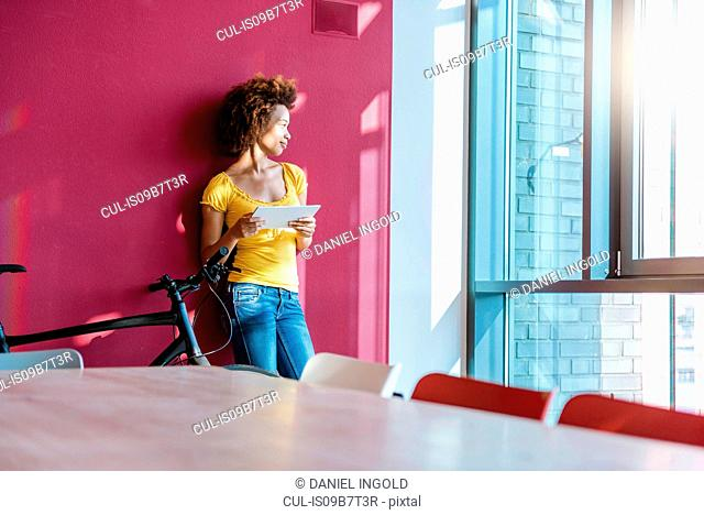 Young woman leaning against wall gazing through window