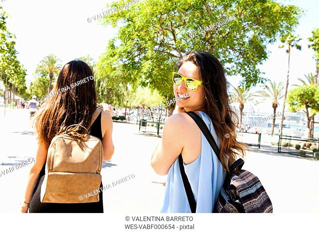 Spain, Barcelona, portrait of smiling woman with sunglasses having a walk with her best friend
