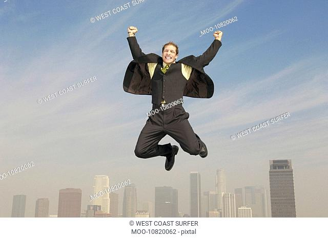 Business man pumping fists mid-air above city