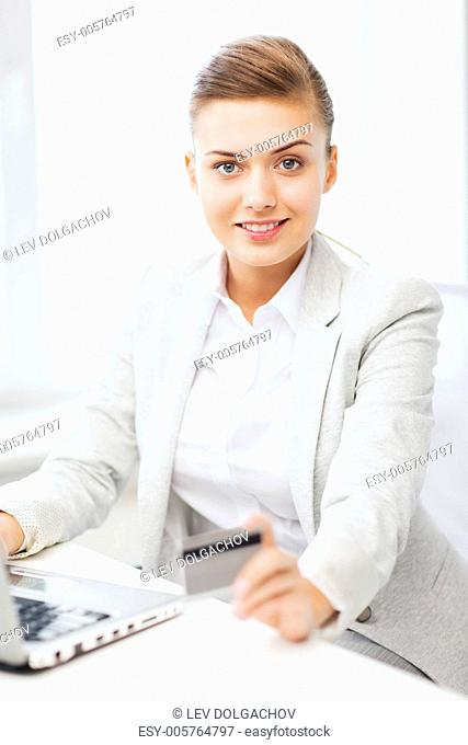 business and internet concept - smiling businesswoman with laptop using credit card