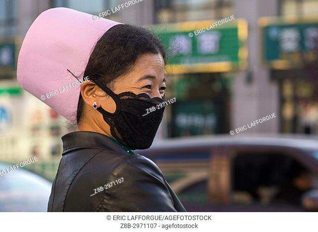 Muslim woman with the traditional pink hat and a mask in the street, Gansu province, Linxia, China