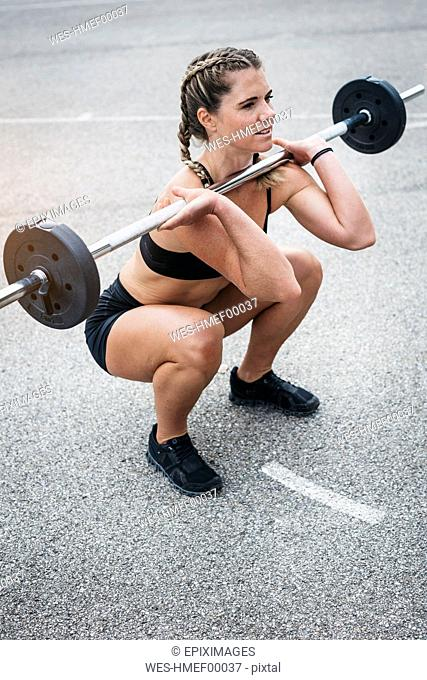 Woman doing barbell exercise during weight lifting workout