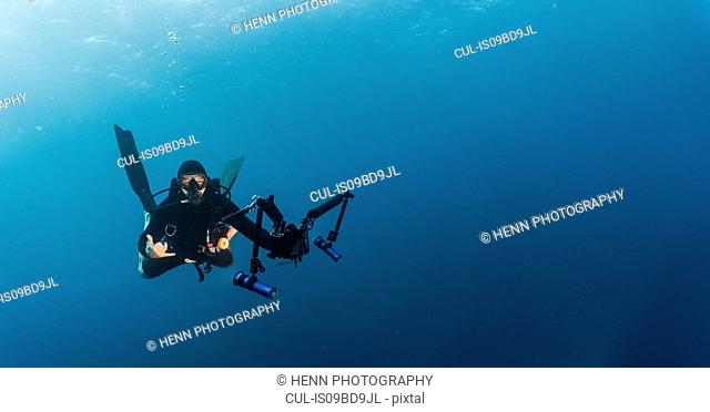 Diver taking selfie with underwater camera, underwater view, Tubbataha Reefs Natural Park, Cagayancillo, Palawan, Philippines