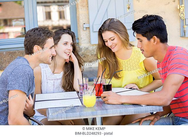 Friends reading menus at restaurant