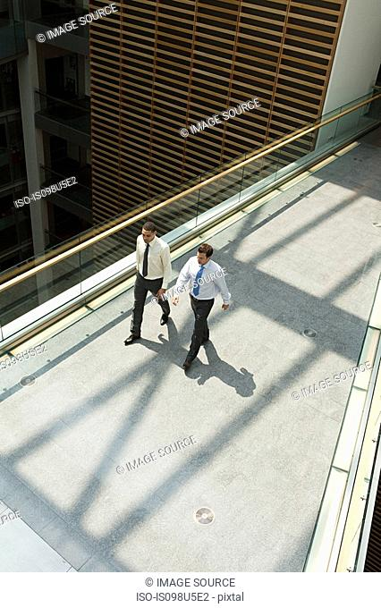 Businessmen walking office walkway