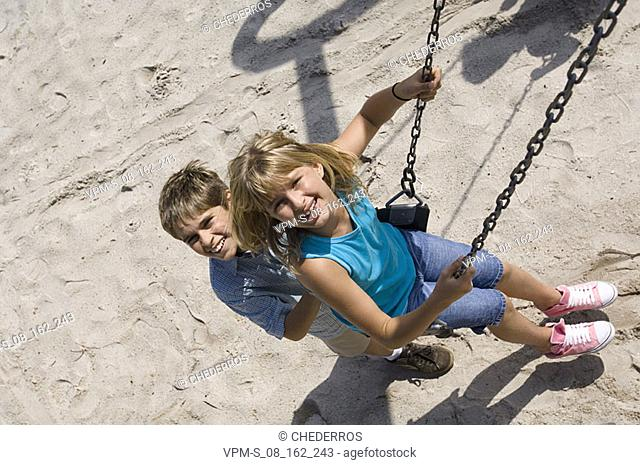 Portrait of a boy pushing a teenage girl on a swing
