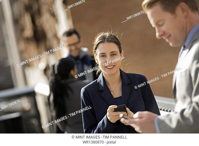 Three people standing on the sidewalk in the city, checking their phones. Two men and a woman