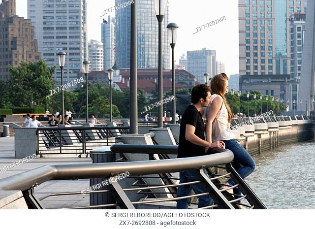 A couple tourists kissing in the Bund. China Love. The Bund promenade, Shanghai, China. China Shanghai Tourist Shanghai Skyline viewed over the Huangpu river...