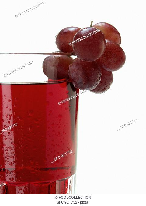 Red grapes on glass of red grape juice (detail)