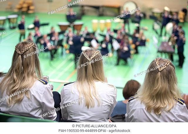 30 May 2019, Lower Saxony, Osnabrück: Members of a Spielmannszug sit with the same hairstyle on a grandstand at the 5th German Championship - Concert rating...