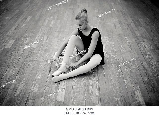 Caucasian ballerina tying pointe shoes