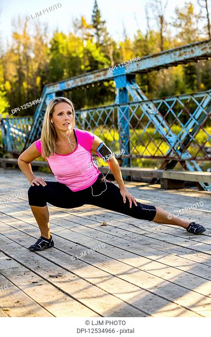 An attractive middle-aged woman listens to music on her smart phone and pauses to stretch out her legs on a bridge during a run on a beautiful warm fall evening...