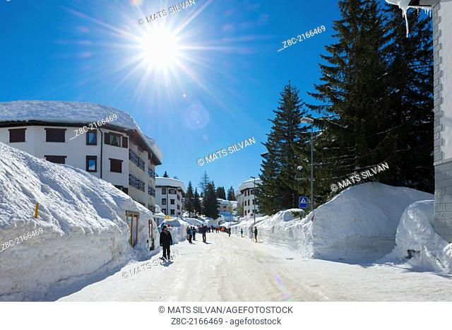 Main street with snow walls and sunshine in San Bernardino, Grisons Switzerland