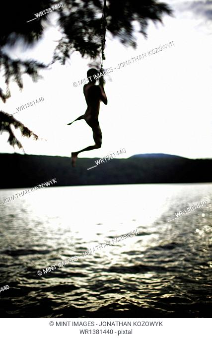 Boy jumping off rope swing