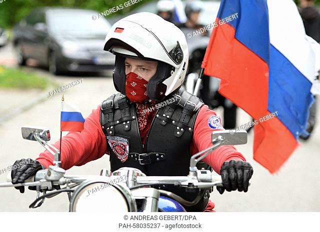 A supporter of the Russian bikers' club 'Night Wolves' carries a Russian flag on his motobike as he drives across the visitors' parking lot at the concentration...