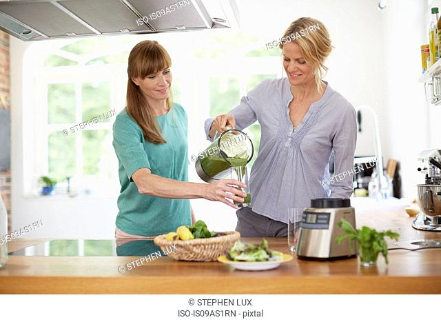 Women drinking green vegan smoothie in kitchen