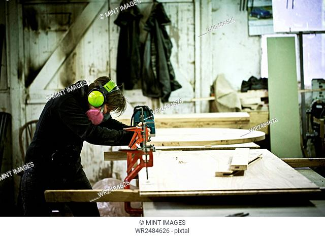 A woman working in a furniture maker's workshop cutting timber with a saw