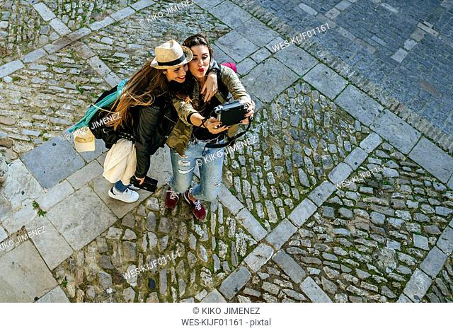 Two happy young women taking a selfie with a camera