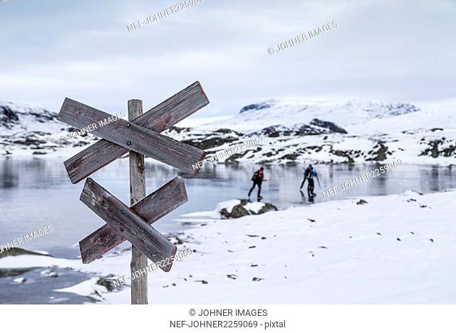 People skiing on frozen lake