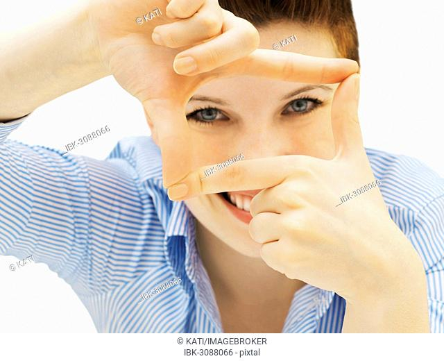 Businesswoman looking through her fingers as a frame