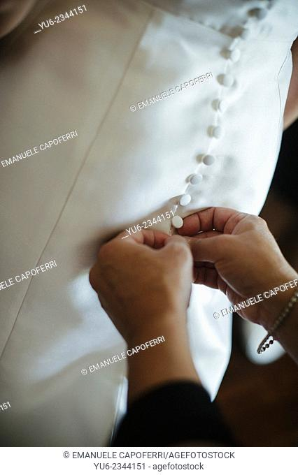 Hands belt buttons of the wedding dress
