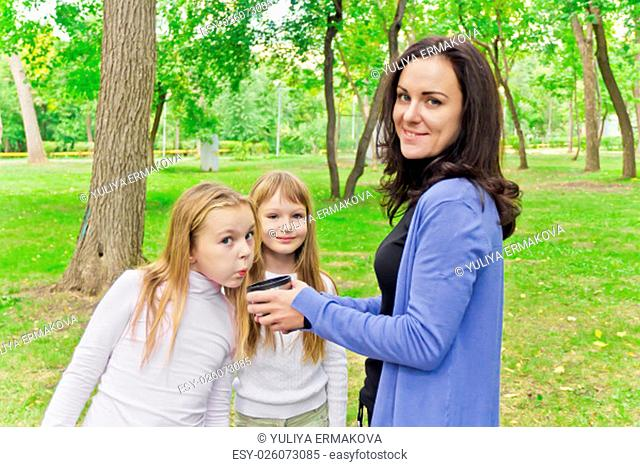 Photo of woman with two girls drinking tea