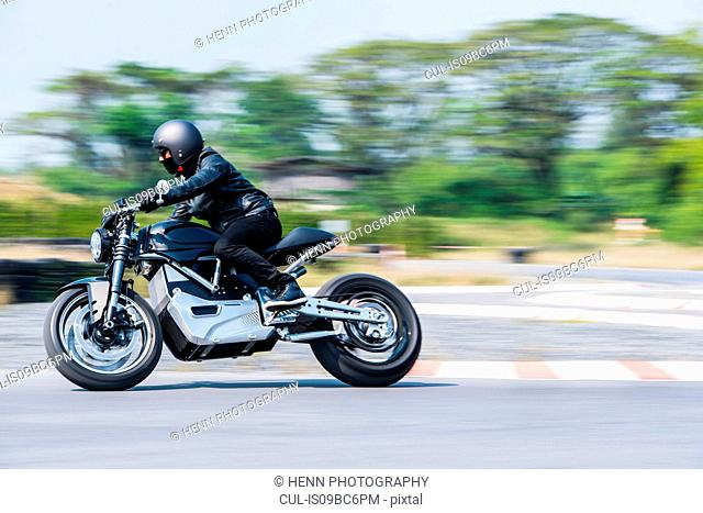 Man testing electric cafe racer motorbike on race track