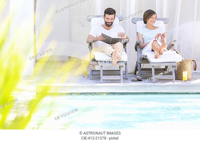 Couple relaxing in lawn chairs by swimming pool