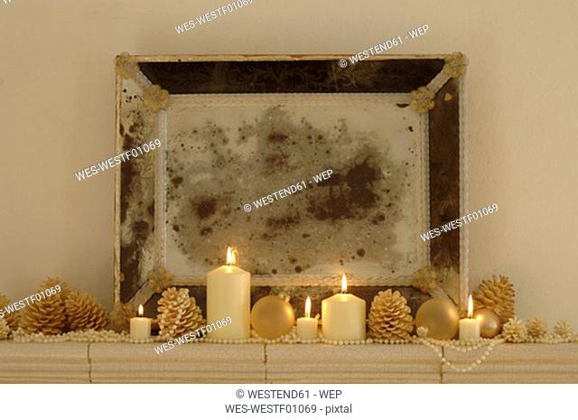 Burning candles with fir cones and frame on shelf , close-up