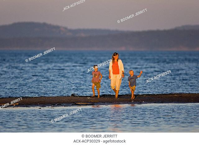 A mother and children stroll along a sandbar at low tide at Sidney Spit Marine Park near Sidney on Southern Vancouver Island