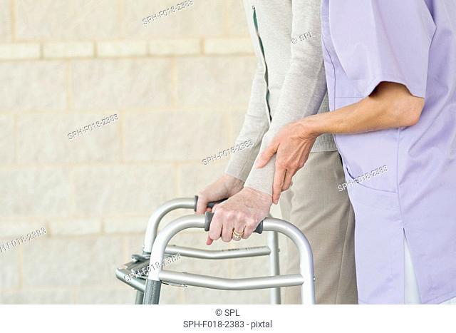 Senior woman using walking support frame