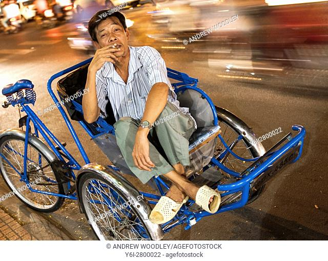 Rickshaw operator waits for customers Ho Chi Minh City Vietnam