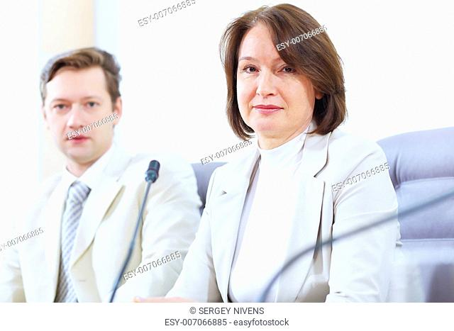 Image of two businesspeople sitting at table at conference